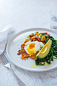 Sweet potato cake with poached egg, spinach, avocado and tomatoes