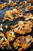 Spicy marinated, oven-baked cauliflower on a baking tray
