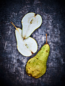 A whole pear and a halved pear on a grey metal surface