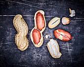 Ganze und aufgebrochene Erdnüsse auf grauem Metalluntergrund