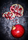 A whole pomegranate and a split pomegranate on a grey metal surface