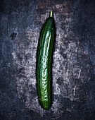 A cucumber on a grey metal surface