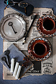 Old newspaper, vintage pewter plate, coffee cups, candles and key