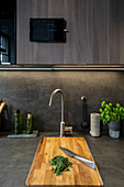 Geschnittene Gewürze auf einem Holzbrett in grauer Küche