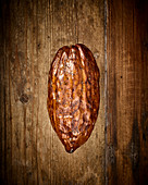 A cocoa pod on a wooden background