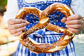 A woman holding a big pretzel