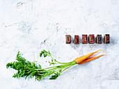 Möhren mit Grün und Holzstempel, die das Wort 'Orange' bilden