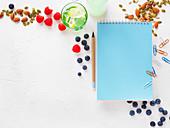 Stilleben mit Notizbuch, Heftklammern, Beeren und Nüssen