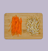 Carrot sticks and mung beans on a wooden board