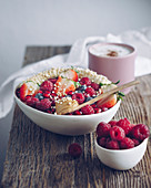 A porridge bowl with fruits, coffee and raspberries