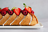 Summery coconut cake with icing, raspberries and strawberries