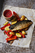 Smoked mackerel on parchment paper with berry sauce