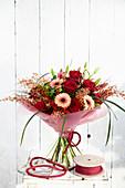 Strauß aus roten Rosen, Gerbera und Ginster