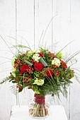Strauß mit roten Rosen und Johanniskrautfrüchten