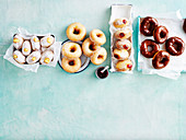 Viererlei Donuts mit Custard Cream, Zitronenglasur, Marmeladenfüllung und Schokoglasur