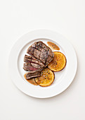 Beef fillet in a lardo coating with orange and bay leaves