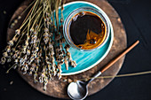 A glass of coffee with dried lavender flowers