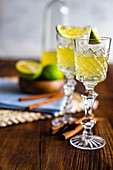 Traditional italian lemon alcohol drink limoncello with pieces of lemon and rosemary herb