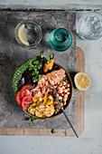 Bowl mit Lachsfilet, Gemüse und Hummus