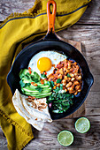 Frying pan with Beans, Avocado, Tomatoes, Eggs and Bread
