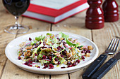 Beetroot, Sprout and Pomegranite Salad on a wooden table with glass of Red Wine