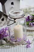 Kerze im Einmachglas mit Hyazinthen und Wachteleiern
