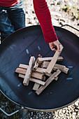 Holz in Feuerschale schichten