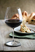 A glass of red wine, with Neapolitan Easter bread in the background