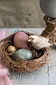 Colourful eggs and golden bird in Easter nest