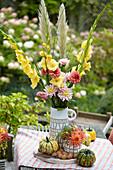 Tischdekoration mit Dahlien, Gladiolen und Kürbissen