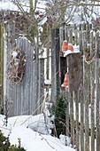 Gartentor mit Kranz und Töpfe am Zaun im winterlichen Garten