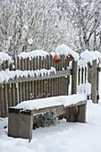 Verschneite Bank am Gartenzaun
