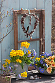 Töpfe mit Primeln und Strahlenanemone vor Fensterflügel mit Herz aus Weidenkätzchen