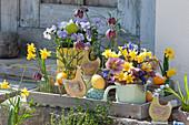 Osterdeko auf Holztablett: Narzissen, Hornveilchen, Schachbrettblumen, Lenzrosen und Netziris, Holz-Hühner und Ostereier
