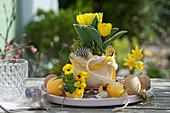 Oster-Tischdekoration mit Tulpe und Hornveilchen, Ostereiern und Federn