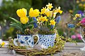 Kleine Frühlings-Tischdekoration mit Tulpen, Narzissen und Traubenhyazinthen in Tassen