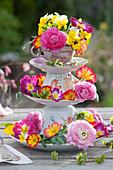 Selbstgebaute Etagere aus Tassen und Tellern mit bunten Frühlingsblumen