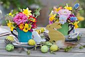 Kleine Oster-Tischdekoration mit bunten Sträußchen in Tassen, Ostereiern und Osterhase