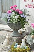 Blumenspindel mit Frühlingsblumen und Weidenkranz als Osternest mit Ostereiern und Osterhasen