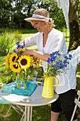 Frau steckt Strauß aus Sonnenblumen und Rittersporn