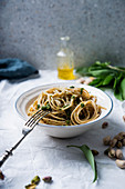 Wholemeal spaghetti with wild garlic and pistachio nut pesto and almond cheese substitute (vegan)
