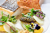 Bass with caviar, vegetables and edible flowers