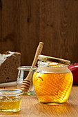 jar of honey with honeycomb in ray of sunlight