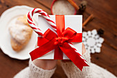 Hands of woman holding Christmas present with candy cane