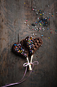 Vegan waffle hearts on sticks with chocolate glaze and colourful sugar sprinkles