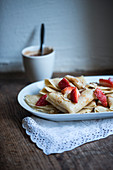 Vegan crepes with strawberries, chocolate sauce and roasted almonds