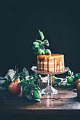 A layered apple cake with a caramel topping and apple leaves