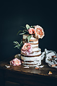 A wedding cake (naked cake) with pastel-coloured summer flowers