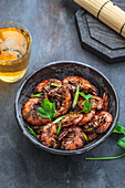 Black pepper prawns in a bowl with beer