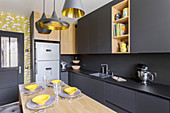 Black designer kitchen with central dining area